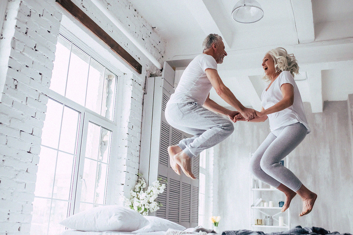 old-senior-couple-jumping-on-bed-having-fun