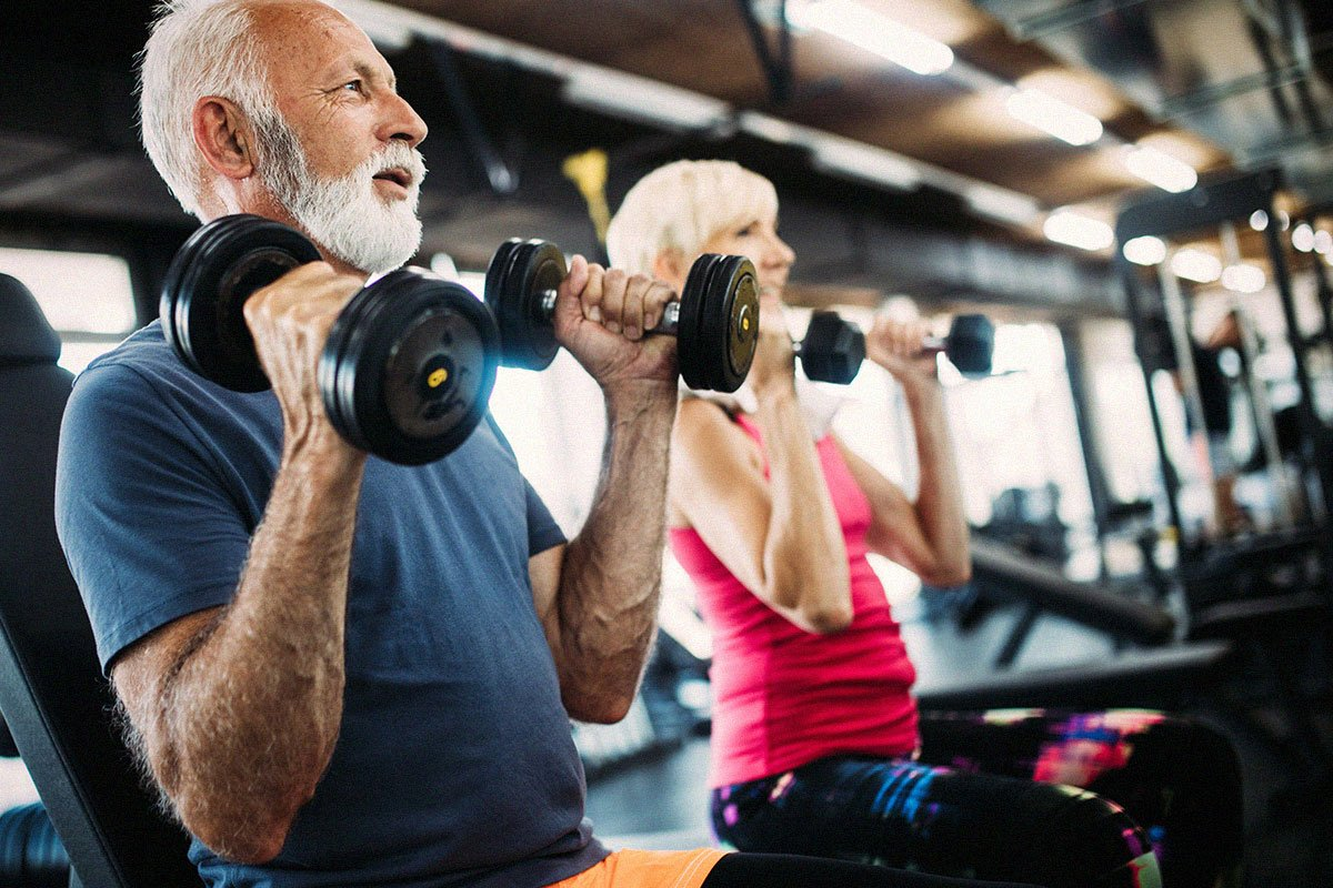 senior-couple-excercising-and-lifting-weights-at-gym